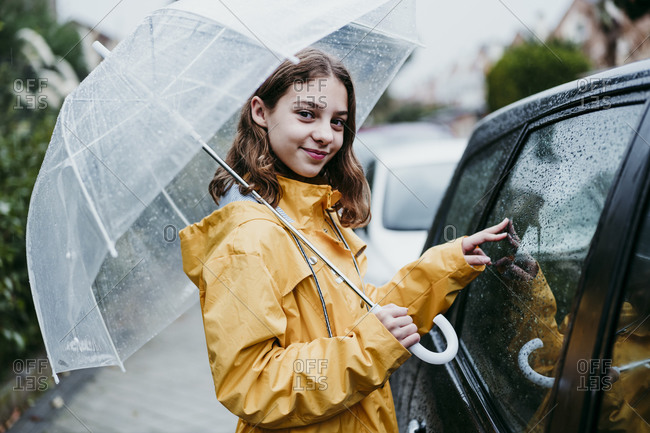 Smiling girl in raincoat holding umbrella while standing by car in city