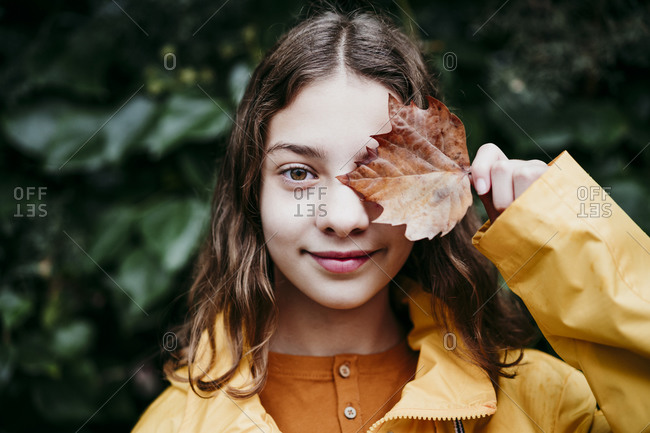 Smiling girl in raincoat hiding eye with dry ivy leaf while standing against leaf wall