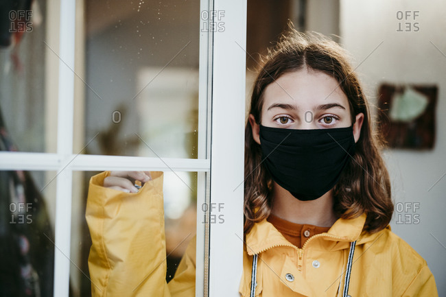 Girl wearing raincoat and face mask standing by door at home