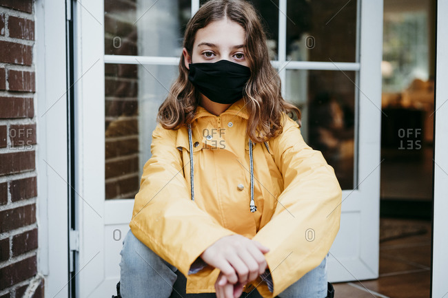 Girl wearing protective face mask sitting on floor against door