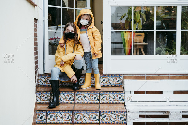 Sisters wearing protective face mask standing and sitting on staircase against door