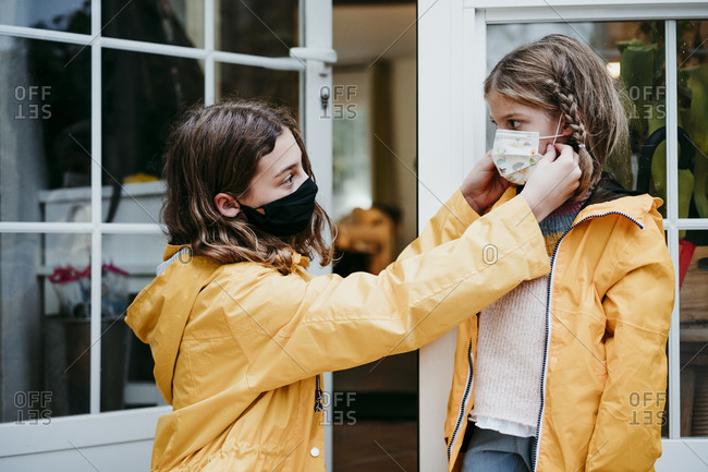 Sister adjusting face mask of sister while sitting against door