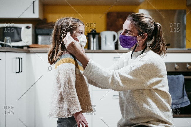 Mother adjusting daughter face mask while sitting at home