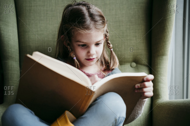 Girl reading book while sitting on chair at home