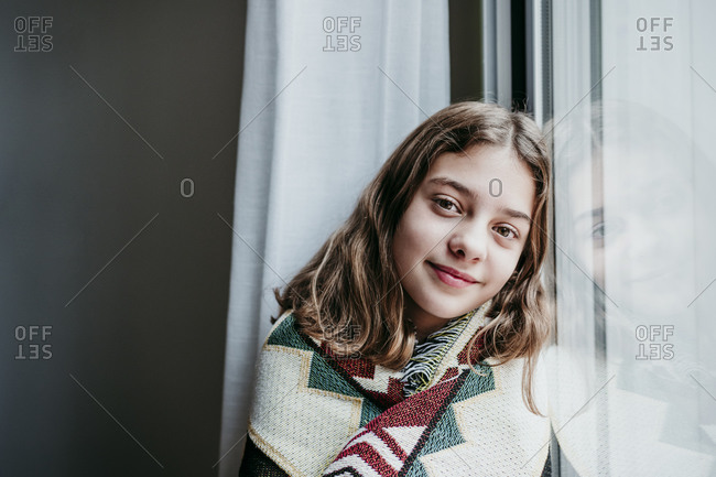 Smiling girl covered in blanket sitting by window at home