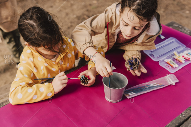 Sisters coloring pine cones at picnic table in park