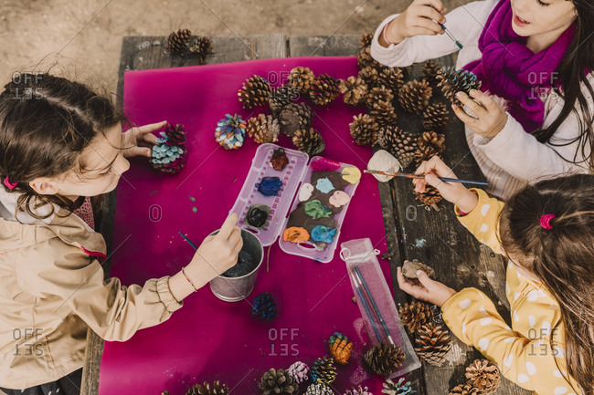 Sisters decorating pine cones while coloring at picnic table in park