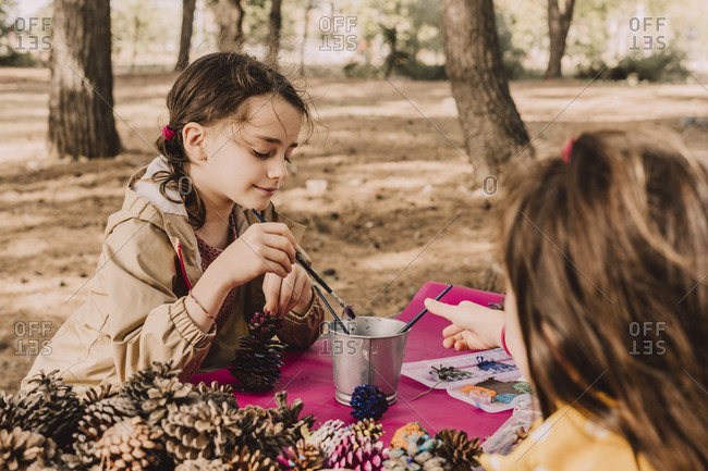 Cute sisters coloring while sitting with pine cones at picnic table in park