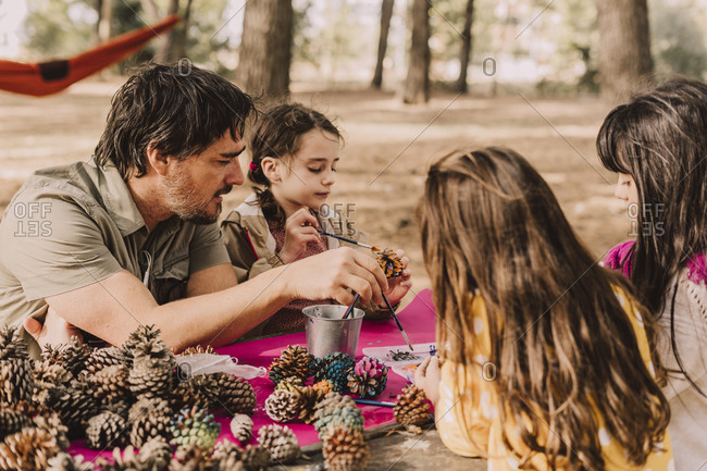 Mature man with daughters decorating while coloring pine cones at picnic table in park