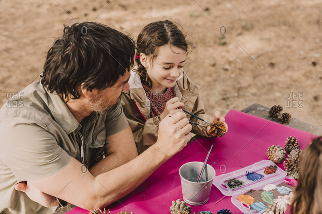 Smiling girl coloring pine cone with father while sitting at picnic table in park