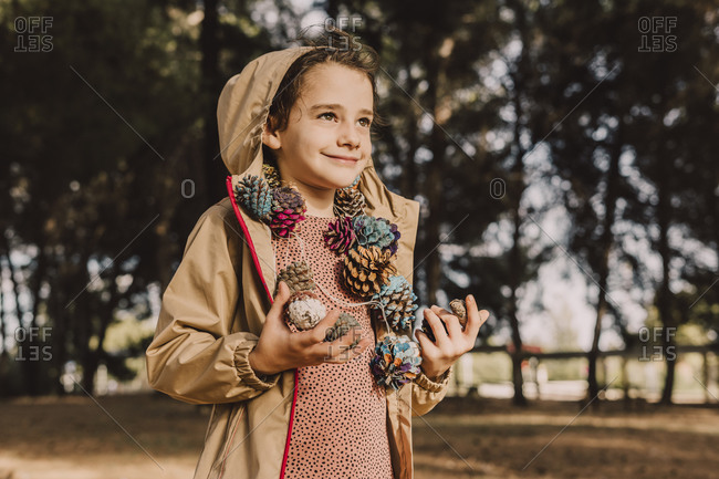 Smiling cute girl with colorful pine cone garland looking away while standing at park