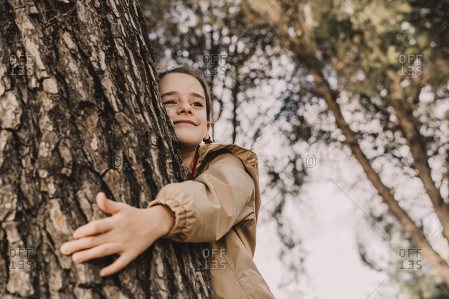 Smiling cute girl hugging tree while looking away at park