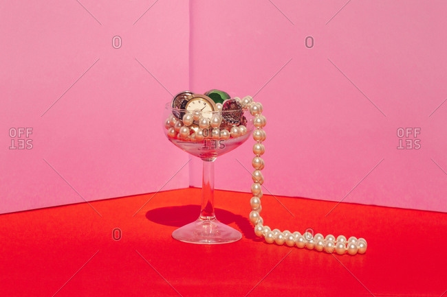 Studio shot of martini glass filled with expensive jewelry