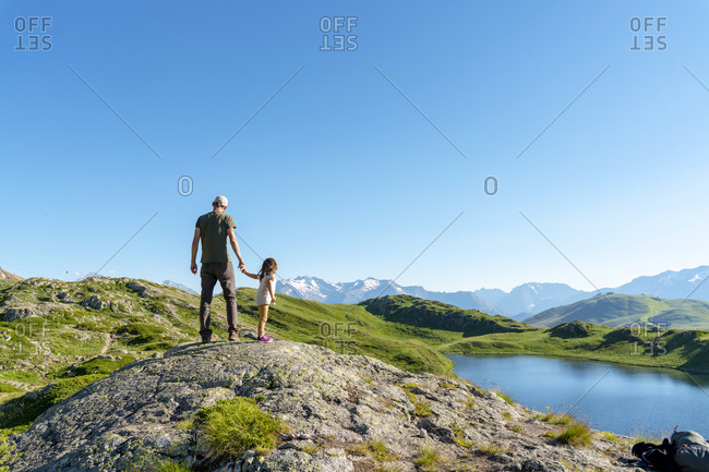 Father and daughter standing on rock object looking at view against clear sky