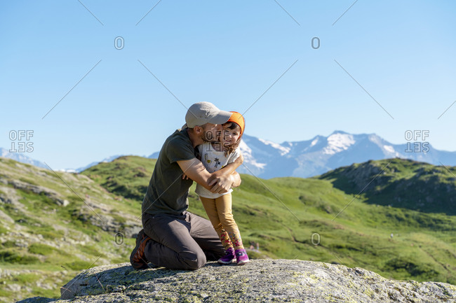 Father kissing daughter while kneeling on rock during sunny day