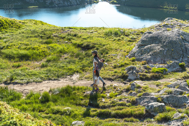 Mother hiking in mountain with daughters on sunny day during summer