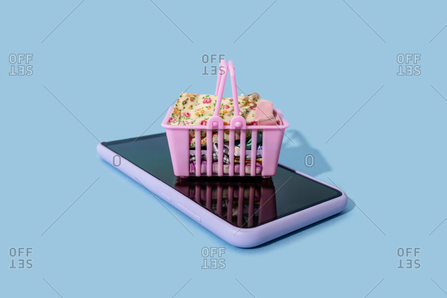 Miniature shopping basket lying on top of smart phone