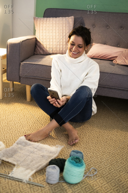 Smiling woman using smart phone while sitting with knitting material on floor at home