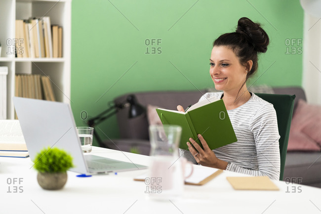 Smiling woman writing in note pad while sitting on chair at home