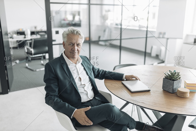 Confident businessman sitting on chair by table at office