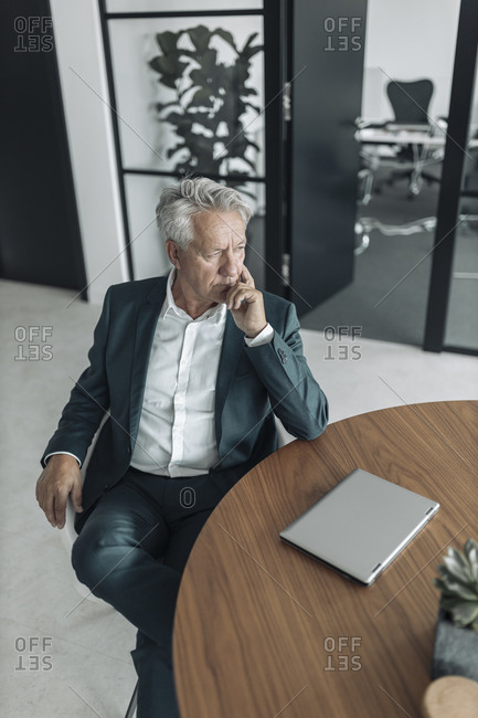 Thoughtful businessman sitting on chair by table at office