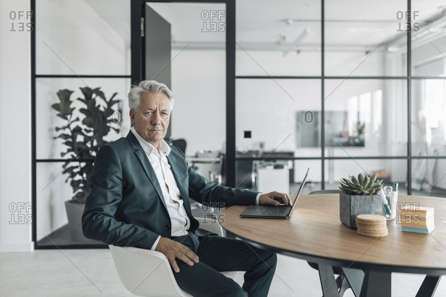 Senior man wearing suit using laptop while sitting on chair at office