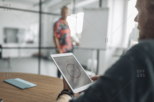 Colleague looking at diagram on digital tablet screen while sitting with businessman in background at office