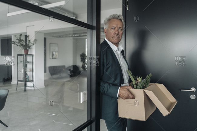 Businessman holding box of botany plant while leaning on glass wall at office