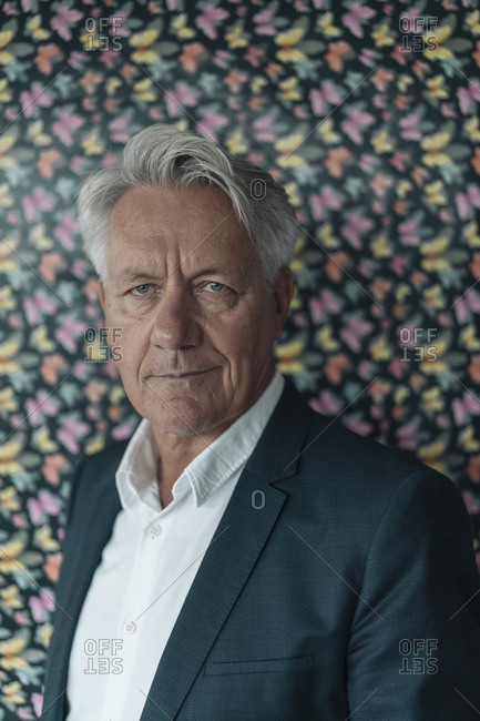 Confident businessman standing against multi colored butterfly pattern wall at office