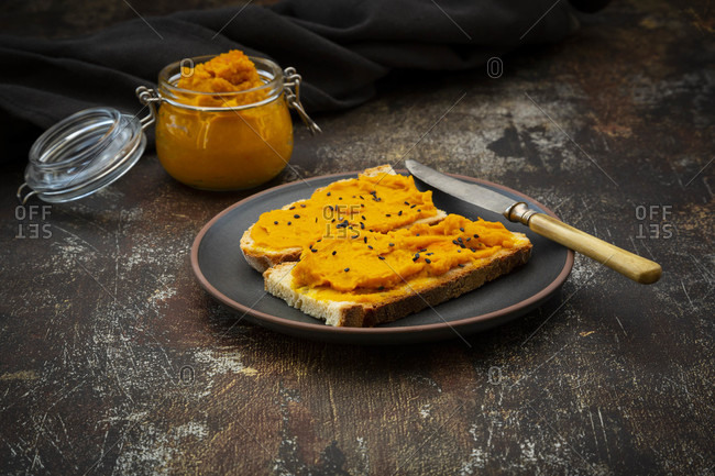 Plate of bread slices with vegan spread made with pumpkin-chick-peasand black sesame seeds