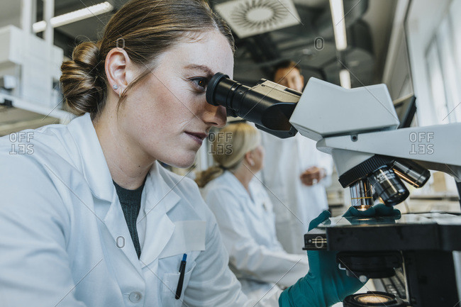 Assistant analyzing human brain microscope slide while sitting with scientist in background at laboratory