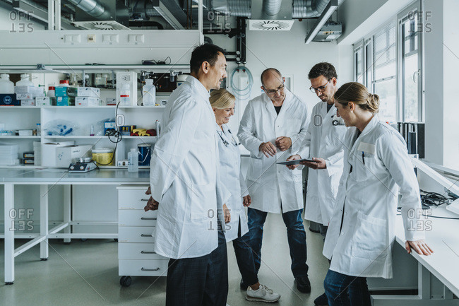 Team of scientist with digital tablet working together while standing at laboratory