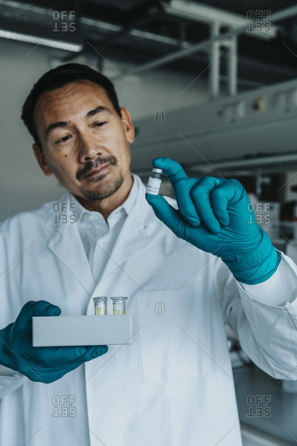 Scientist holding vaccine bottle and test tube tray while standing at laboratory