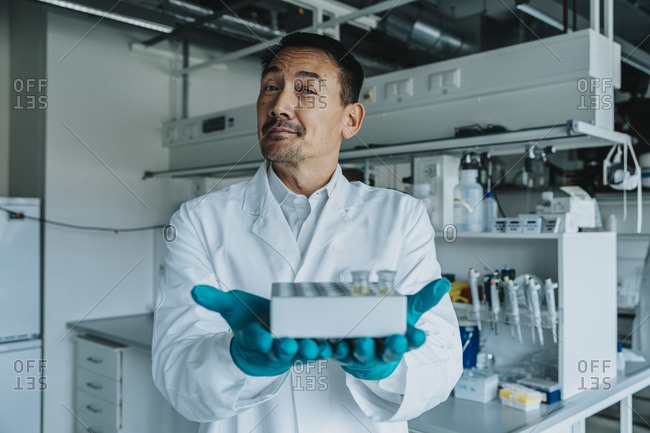 Confident scientist showing test tube tray while standing at laboratory