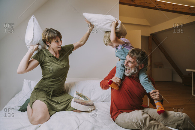 Son sitting on father's shoulder doing pillow fight with mother in bedroom at home
