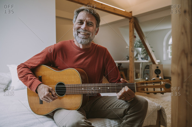 Mature man playing guitar while sitting on bed in bedroom at home