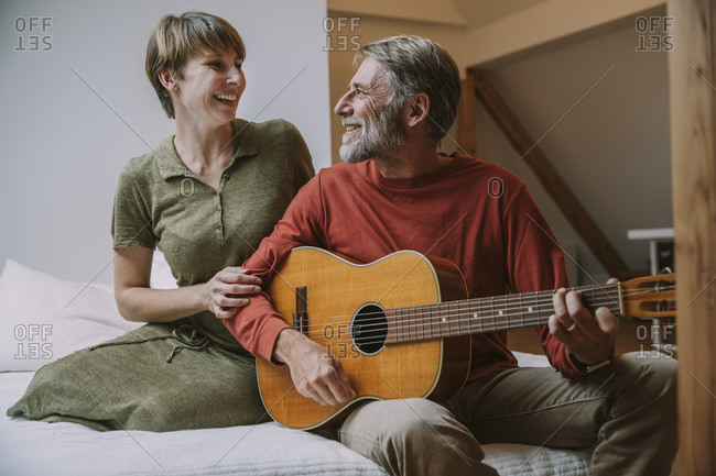 Mature man playing guitar while woman looking at him sitting on bed in bedroom