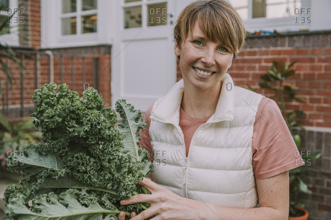 Smiling mid adult woman holding kale leaf while standing in back yard