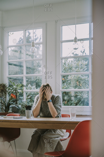 Depressed woman with head in hands sitting at home