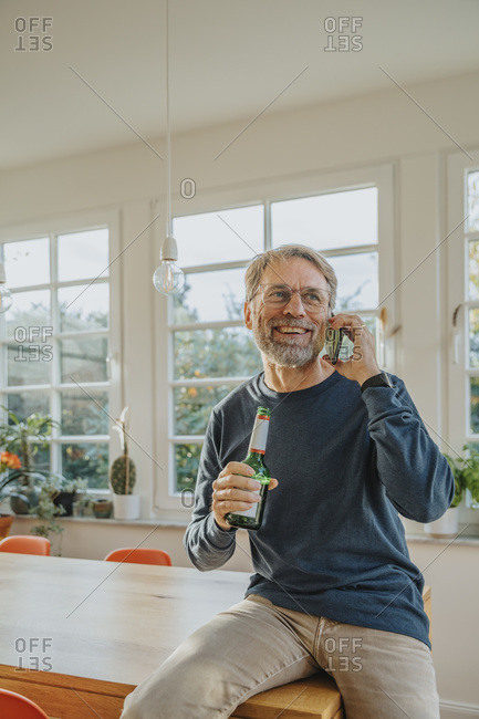 Mature man talking on smart phone while holding beer bottle at home