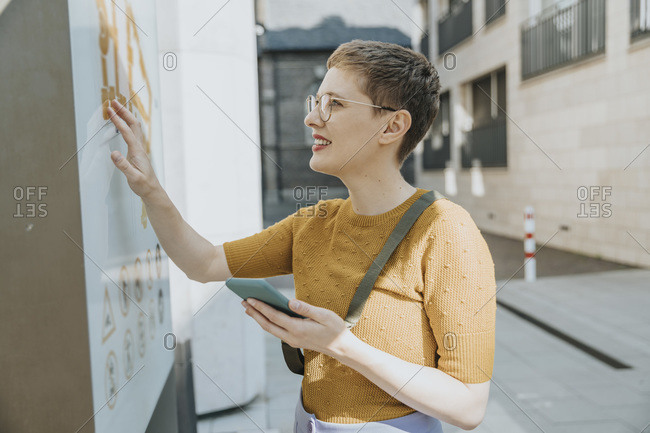 Mid adult woman reading map while holding smart phone standing in city on sunny day