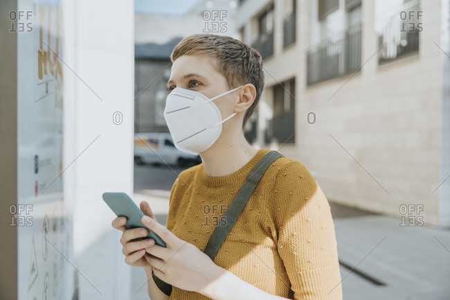 Woman wearing protective face mask reading map while holding smart phone standing in city on sunny day
