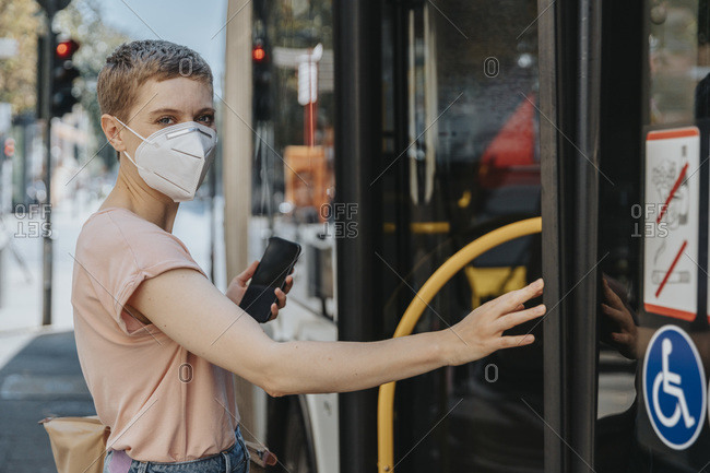 Woman wearing protective face mask catching bus on street in city
