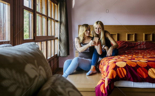 Smiling woman sharing smart phone with teenage daughter while sitting in bedroom at home