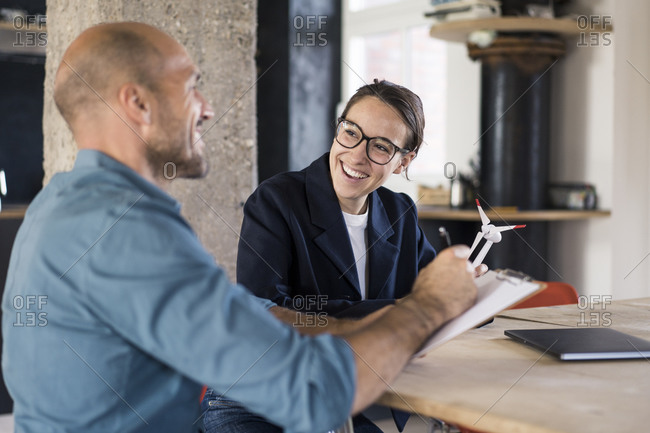 Smiling businessman writing in notepad while working with woman at office