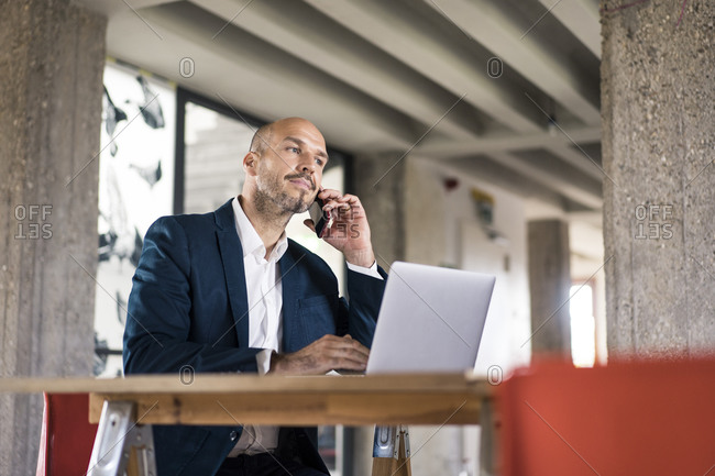 Businessman wearing suit talking on mobile phone while working on laptop at office