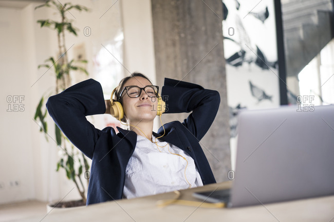 Smiling businesswoman listening music while relaxing on chair at office