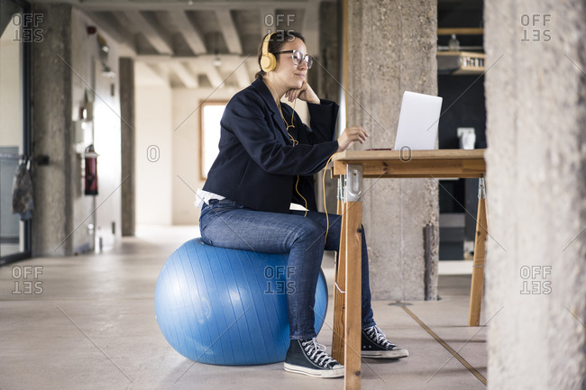 Businesswoman wearing headphones using laptop while sitting on fitness ball at office