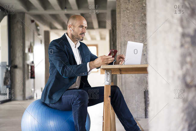 Businessman using mobile phone and laptop while sitting on fitness ball at office