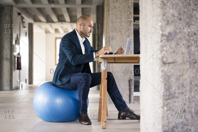 Man using laptop while sitting on fitness ball at office